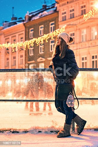 istock Beautiful young woman in fur coat stands by a skating rink border on old snowy European city background 1060116124