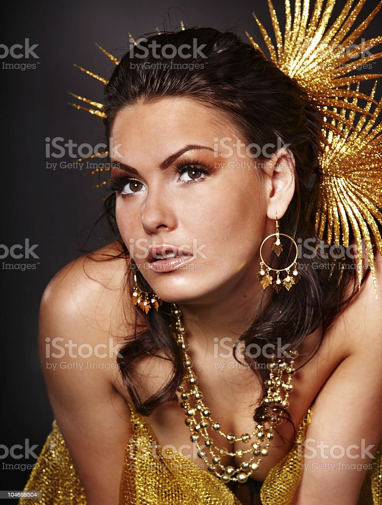Beautiful young woman in gold on grey background. royalty-free stock photo