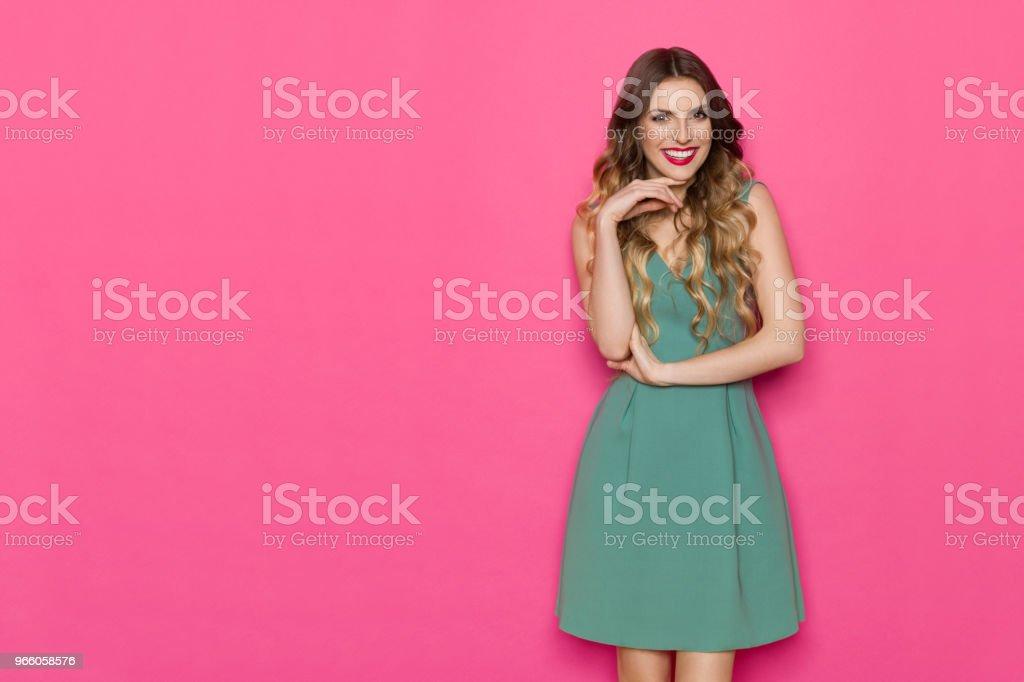Vacker ung kvinna i grön klänning poserar med Hand på hakan - Royaltyfri Elegans Bildbanksbilder
