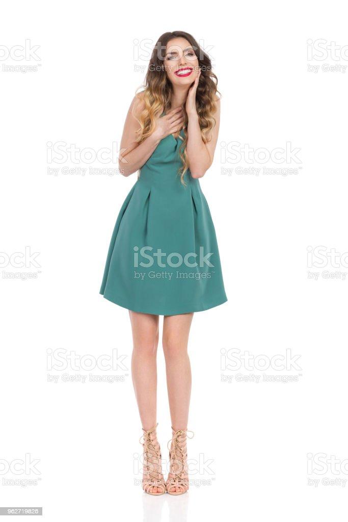 13f226e416 Hermosa mujer joven en Mini vestido verde y zapatos de tacón altos es mano  en la