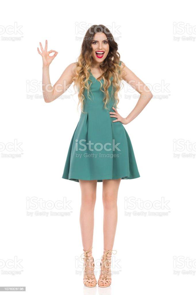 ce9ce5cb1 Hermosa Mujer Joven En Mini Vestido Verde Y Zapatos De Tacón Altos ...