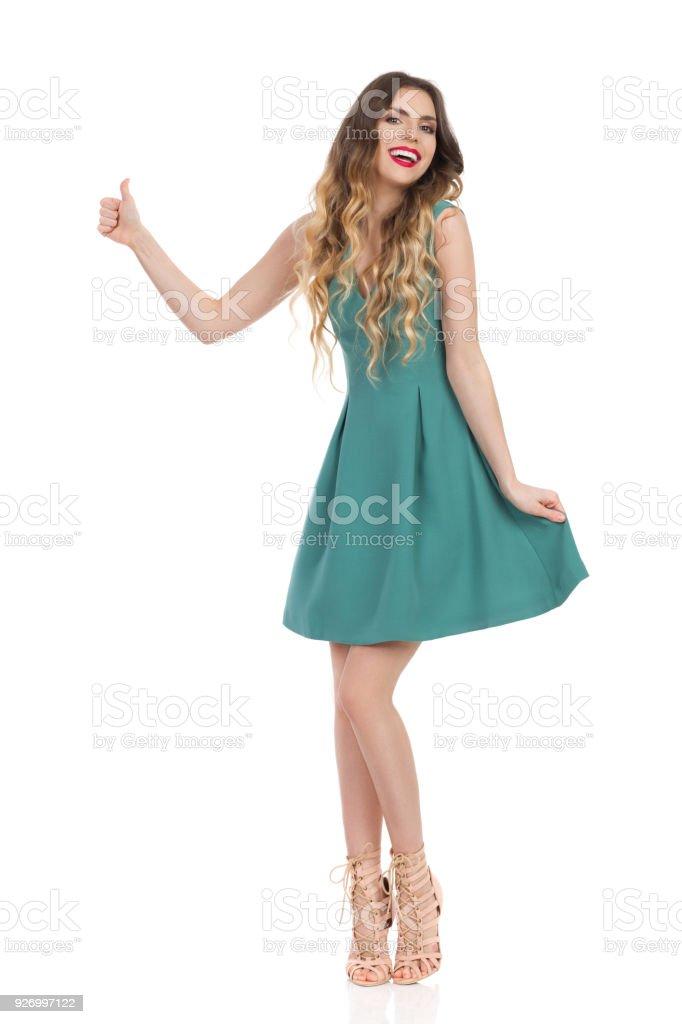 74f937d3e59 Belle jeune femme en robe Mini verte et des talons hauts est montrant le  pouce vers