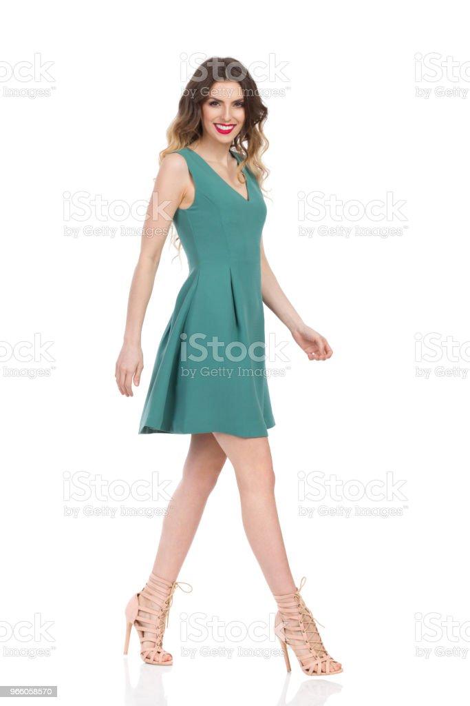 Vacker ung kvinna i grön klänning och högklackat promenader och leende - Royaltyfri Bredbent Bildbanksbilder