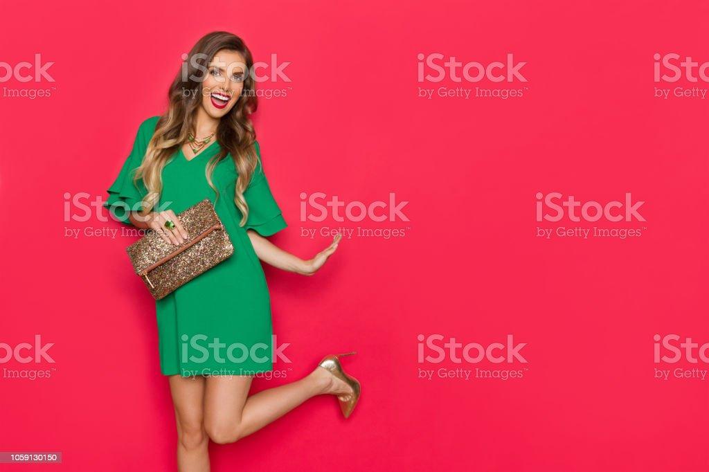 86ca70faf57 Belle jeune femme en robe Mini verte est debout sur une jambe et rire photo  libre