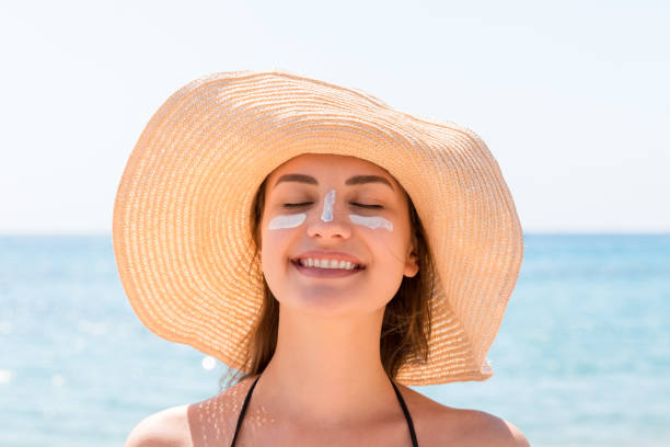 Beautiful young woman in hat is applying sunblock under her eyes and on her nose like Indian. Sun protection concept stock photo