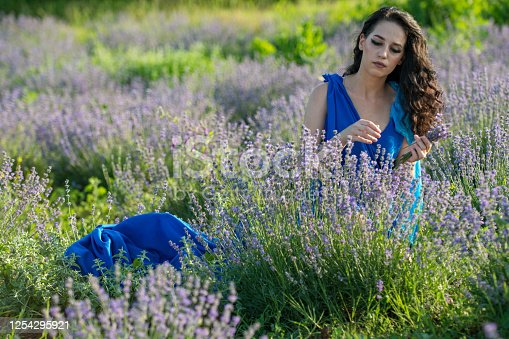 Beautiful young woman in lavender field on summer day wearing blue long dress