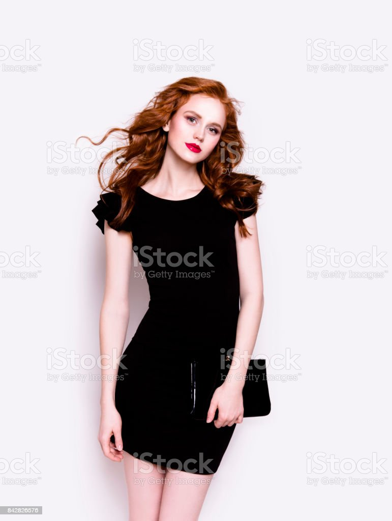 Beautiful young woman in luxury black cocktail dress holding clutch stock photo