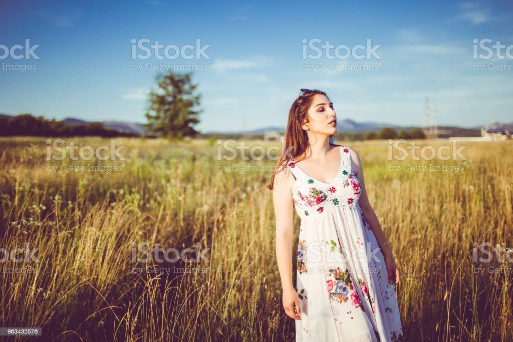 Beautiful young woman in meadow enjoying in sunny day. - Zbiór zdjęć royalty-free (20-29 lat)