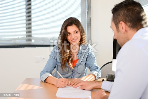 istock beautiful young woman in office with professional finance businessman buying agreement contract signature 669910738