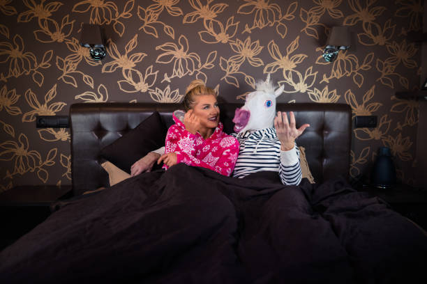 beautiful young woman in pajama lying on the bed with funny boyfriend - unicorn bed imagens e fotografias de stock