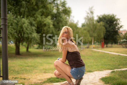 istock Beautiful young woman in park 1058434956