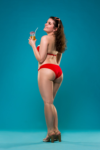 1155046257 istock photo Beautiful young woman in red bikini with cocktail on blue background 689252636