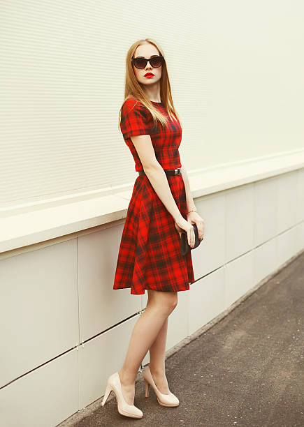 Beautiful young woman in red dress, sunglasses with handbag clut stock photo