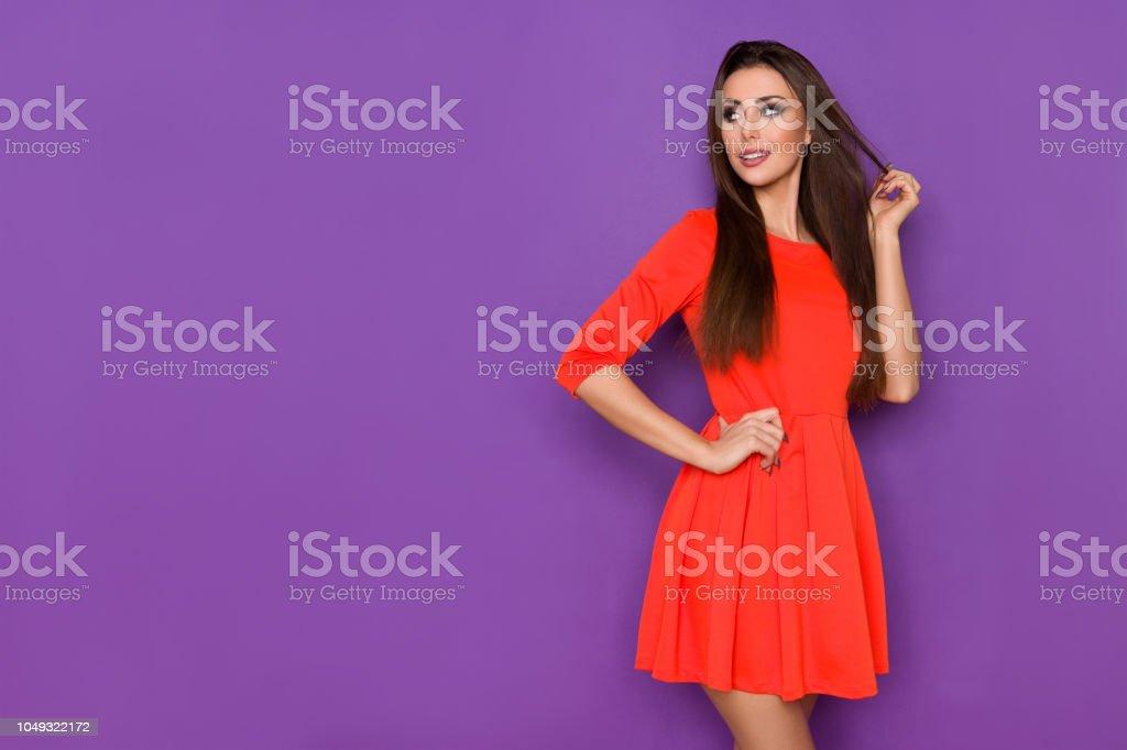 0919329e0bb Photo de stock de Belle Jeune Femme En Robe Mini Rouge Cherche Loin ...