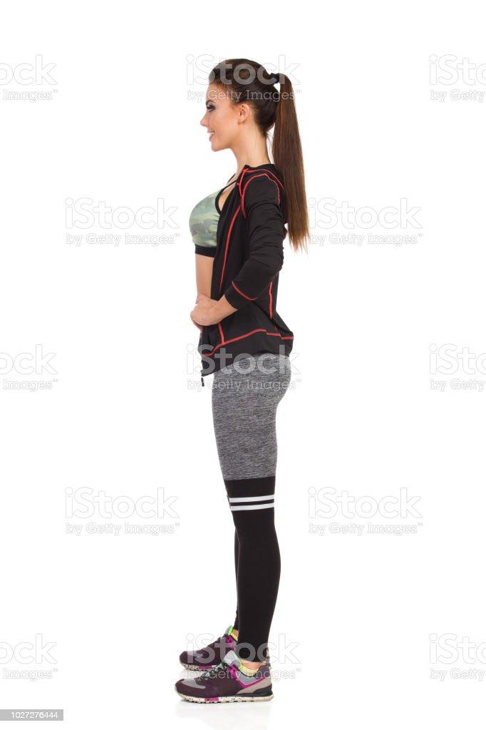 1cdc310d5 Mulher jovem e bonita em roupas esportivas está de pé com mão no quadril.  Vista