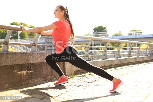 istock Beautiful young woman in sports clothing stretching while standing outdoors. 1170147348