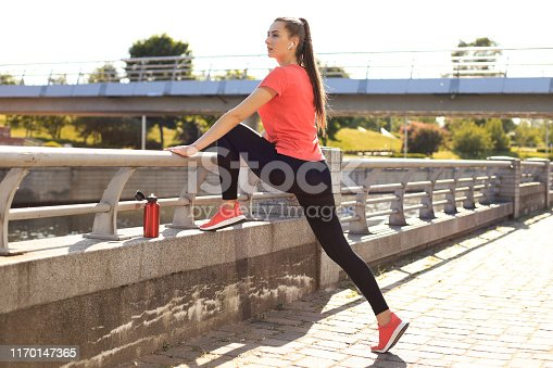 istock Beautiful young woman in sports clothing stretching while standing outdoors. 1170147365