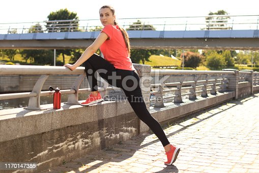 istock Beautiful young woman in sports clothing stretching while standing outdoors. 1170147385
