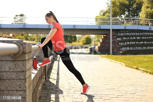 istock Beautiful young woman in sports clothing stretching while standing outdoors. 1170148108