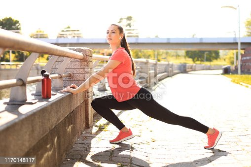 istock Beautiful young woman in sports clothing stretching while standing outdoors. 1170148117