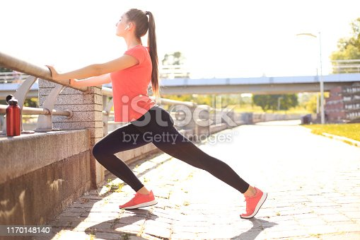 istock Beautiful young woman in sports clothing stretching while standing outdoors. 1170148140