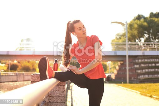 istock Beautiful young woman in sports clothing stretching while standing outdoors. 1170148816