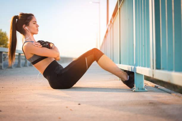 Beautiful young woman in sportswear doing sit ups outdoors stock photo