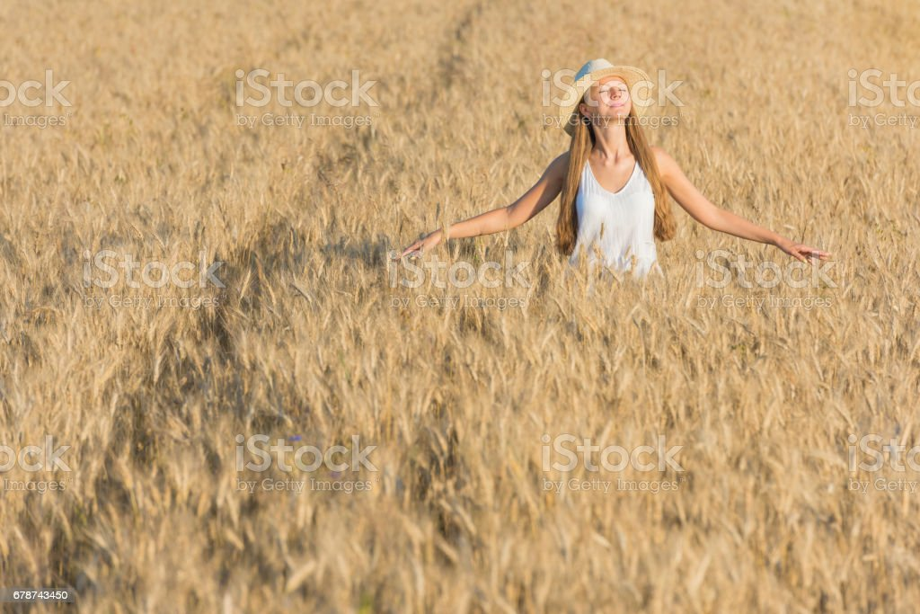 Beautiful young woman in straw hat and white shirt in golden wheat field royalty-free stock photo