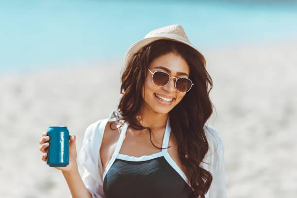 schöne junge frau mit sonnenbrille und strohhut holding cola-dose und lächelt in die kamera - lustige trinkspiele stock-fotos und bilder