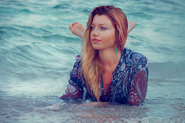 Beautiful young woman in the blue water stock photo