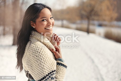 istock Beautiful young woman in the snow in winter 614969294