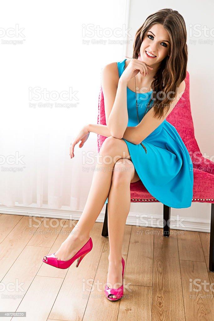 Bela jovem mulher de vestido azul-turquesa sentando na cadeira - foto de acervo