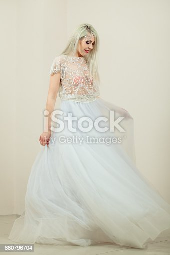 Beautiful young woman in wedding dress posing in studio
