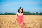 Beautiful woman in wheat field on a hot summer day
