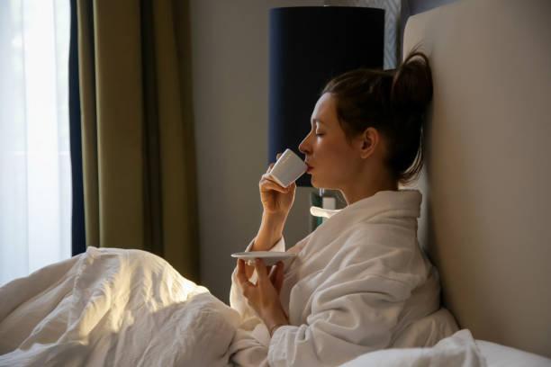 Eine schöne junge Frau im weißen Bademantel trinken Morgenkaffee im Bett – Foto