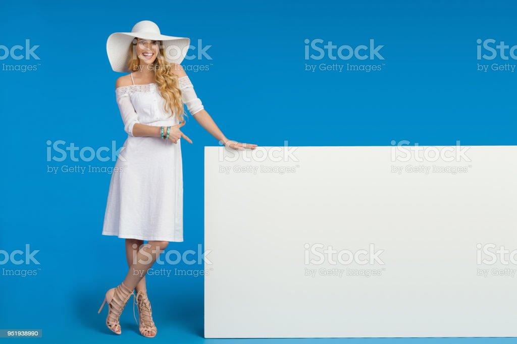 Belle jeune femme en robe blanche et chapeau de soleil pointe à bannière  vide photo libre 898500b387da