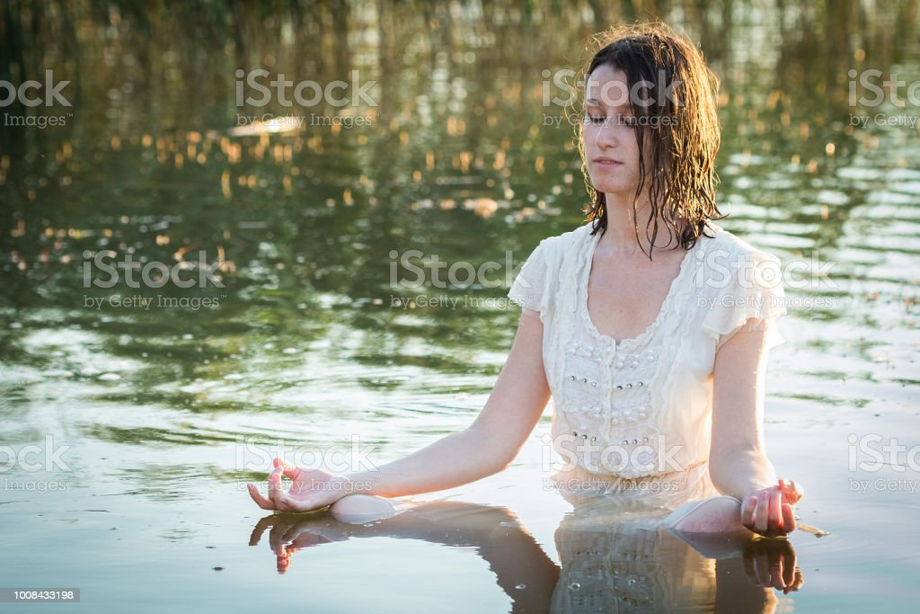 244c8e5428 Beautiful young woman in white dress sitting in a lake and doing yoga  meditation - Stock image .