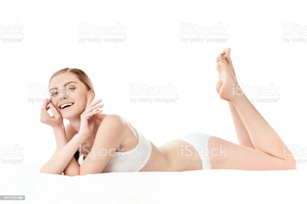 Beautiful young woman in white underwear lying isolated on white, skin care concept royalty-free stock photo