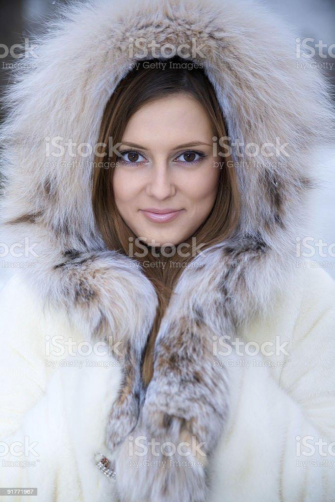 Beautiful young woman in winter fur coat royalty-free stock photo