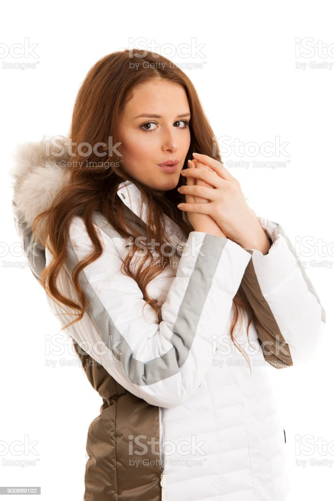 Beautiful young woman in winter jacket  blowing in her ahnds feeling cold isolated over white stock photo