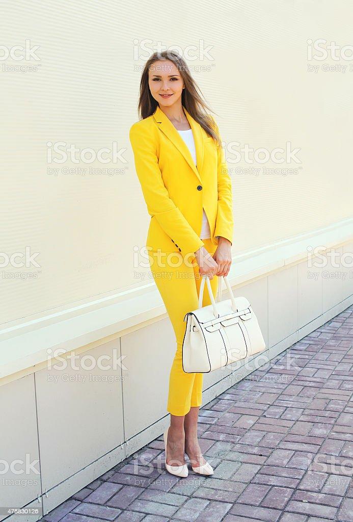 e9b22523b Hermosa mujer joven en traje amarillo ropa con handbag exterior foto de  stock libre de derechos