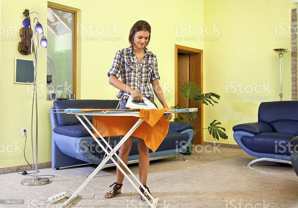 Beautiful young woman ironing his clothes at home. royalty-free stock photo