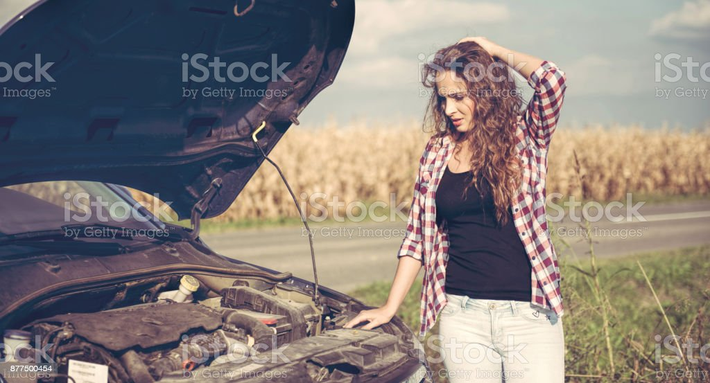 Beautiful young woman is a problem with the car stock photo