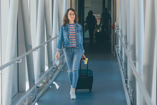 eine schöne junge frau steigt mit ihrem koffer, wagen (handgepäck) in ein flugzeug - druck jeans stock-fotos und bilder