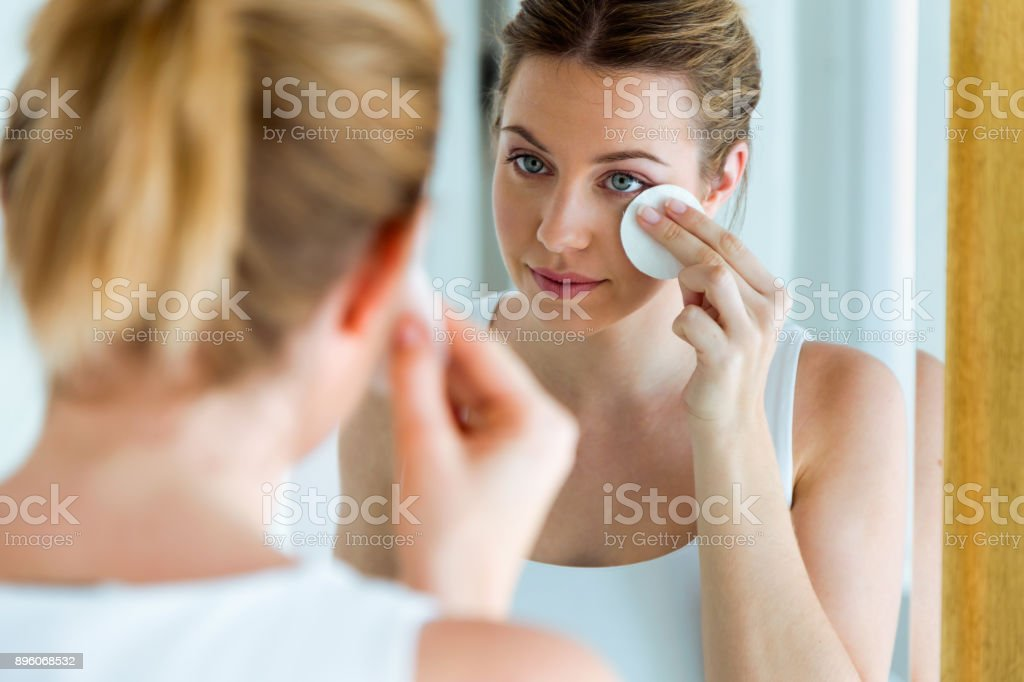 Portrait of beautiful young woman is cleaning her face while looking...