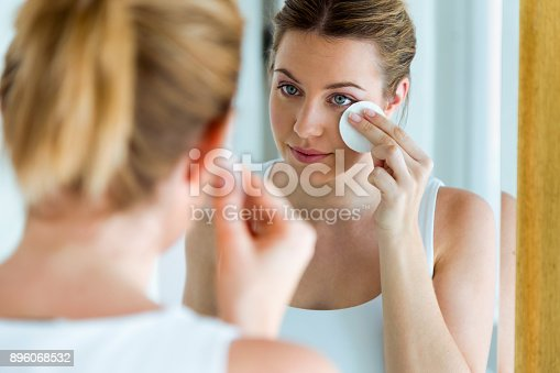 istock Beautiful young woman is cleaning her face while looking in the mirror in the bathroom. 896068532