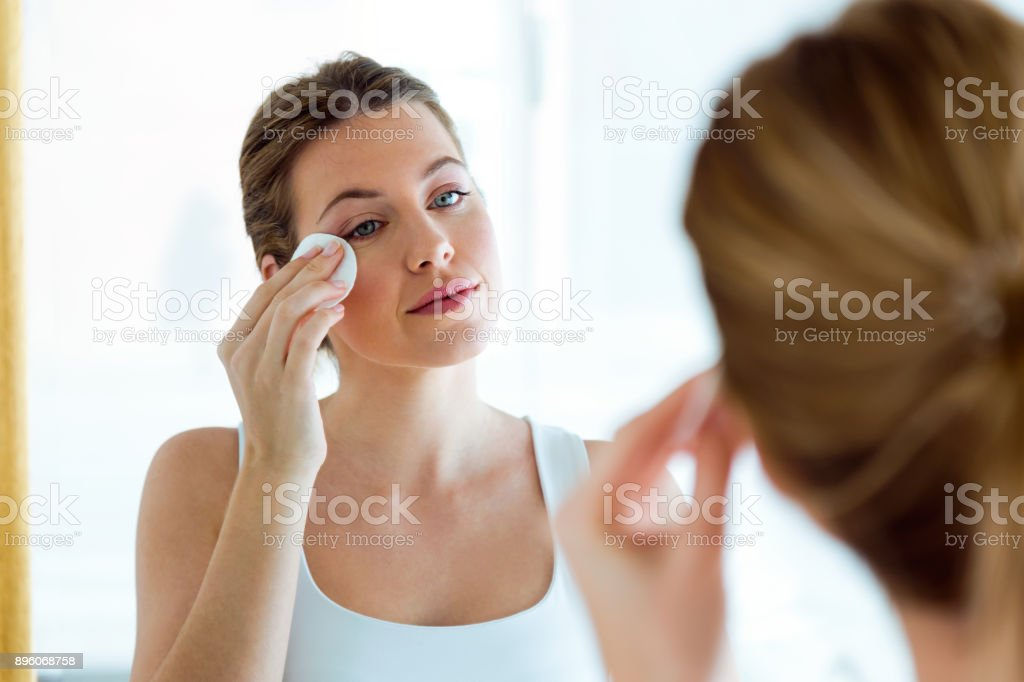 Beautiful young woman is cleaning her face while looking in the mirror in the bathroom. stock photo