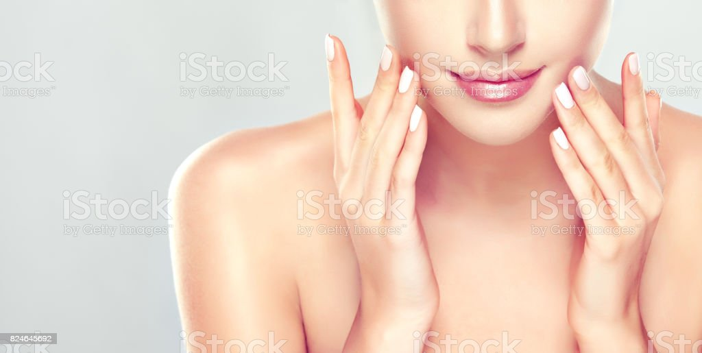 Beautiful young woman is demonstrating process of skin cleaning on the face. Cosmetology. stock photo