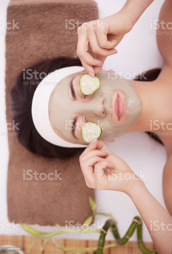 Beautiful young woman is getting facial clay mask at spa, lying with...