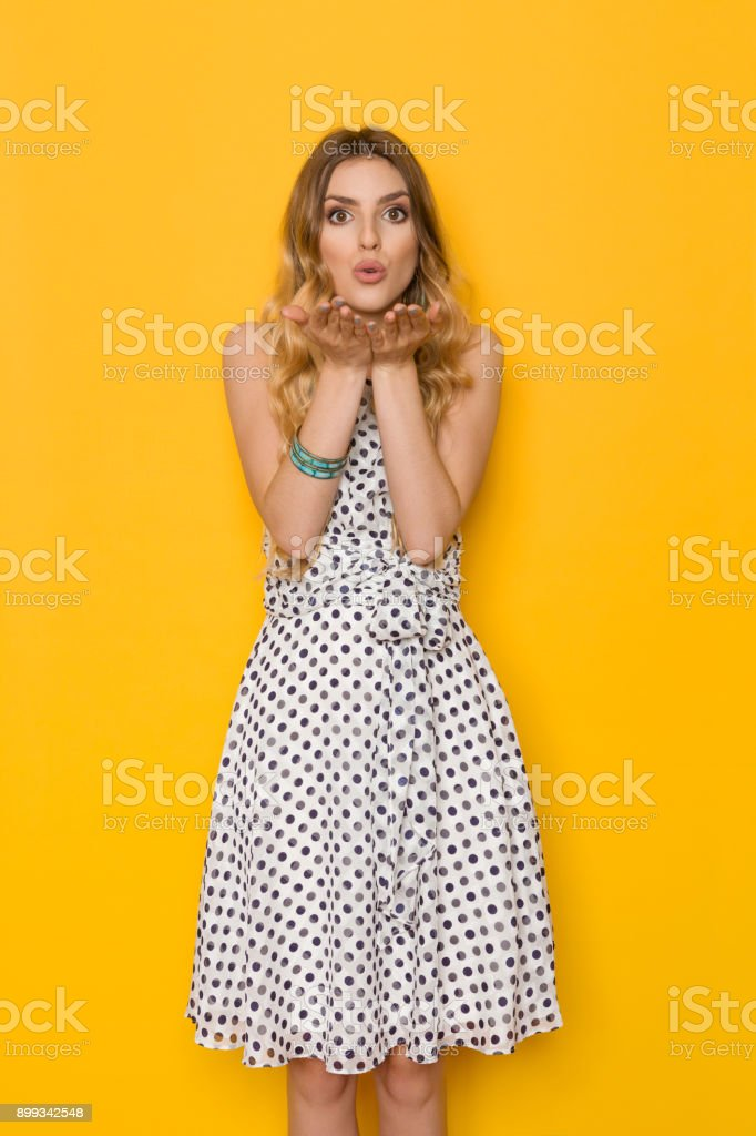 Beautiful Young Woman Is Holding Hand Raised, Looking At Camera And Sending A Kiss stock photo